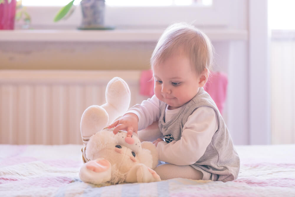 10 months old baby girl playing with a plush bunny