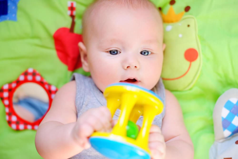 Four month old baby playing grabbing toy