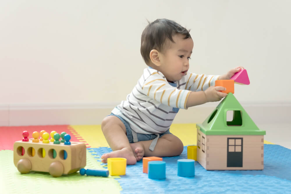 eight month old child reaching for toys